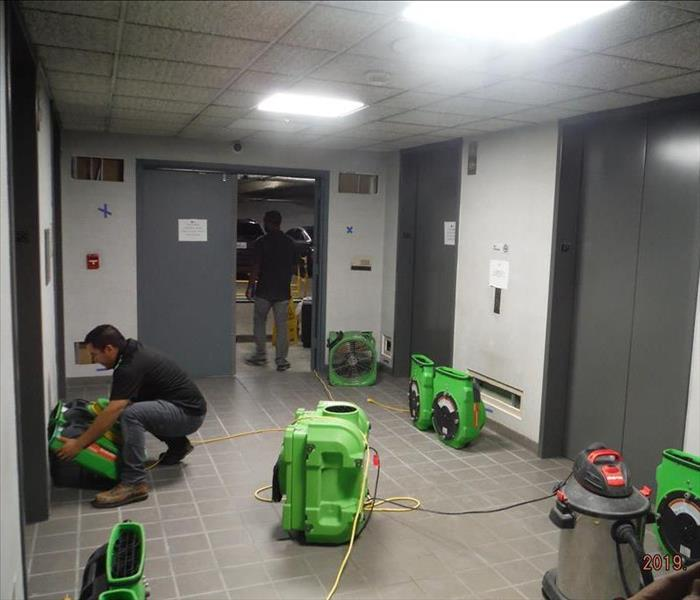 This parking corridor has two uniformed techs setting up bright green drying equipment after the elevators flooded