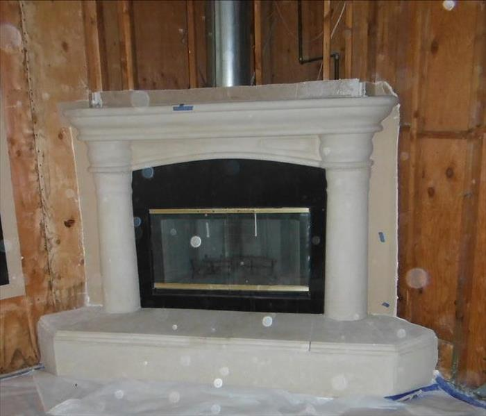 Demolition of surrounding drywall and plaster around this fireplace was necessary due to a roof leak
