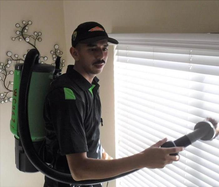 Our professional, uniformed Servpro technician is cleaning the soot damaged blinds using a HEPA Vac to remove tiny particles
