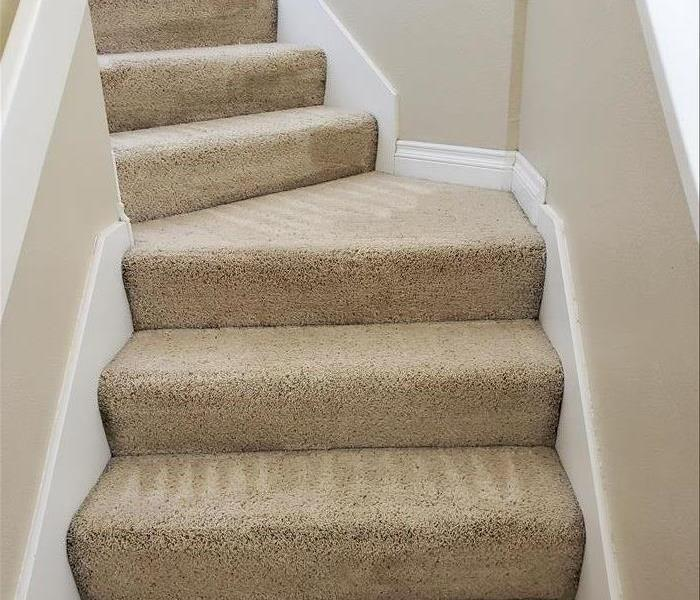 The carpeted staircase previously covered in black ash has been professionally cleaned and looks fresh and bright.
