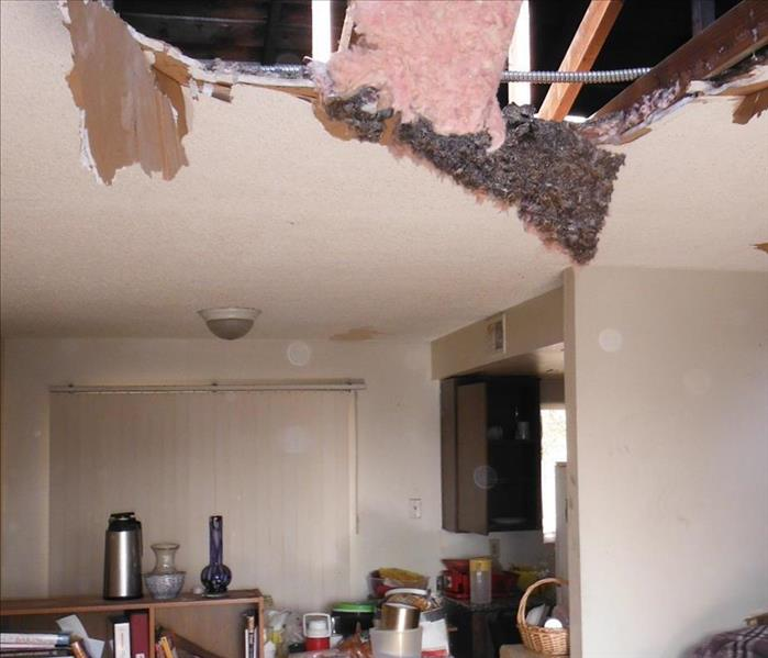 A roof leak from rain soaked the ceiling materials. The heaviness and pressure caused the ceiling drywall to cave in
