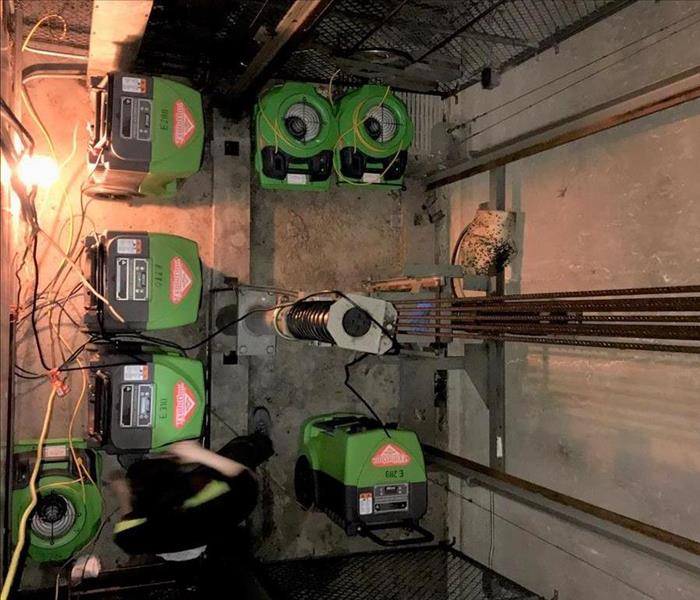 Bright green drying machines operating at the very bottom of this wet elevator shaft that had flooded on an upper level