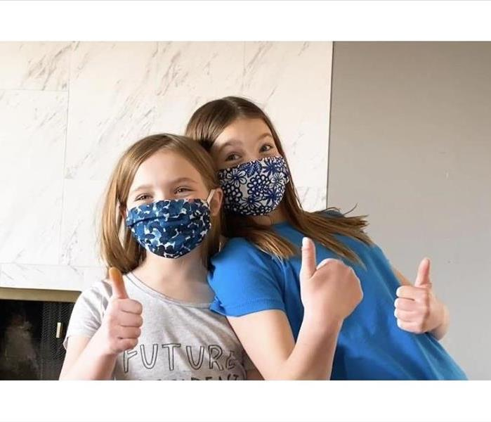 A square blue scarf has two elastic ties attached then is folded to create a homemade washable face mask