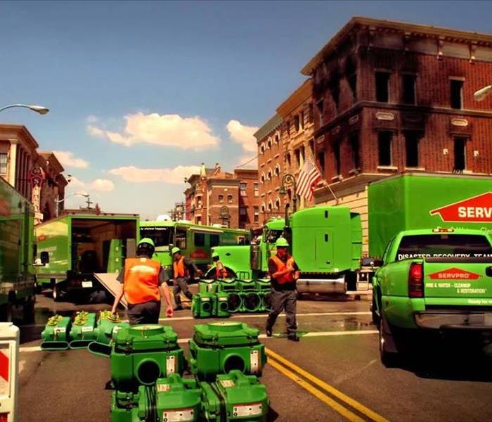 At a city intersection with a burned brick building, SERVPRO professionals are unloading equipment to start restoration